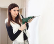 Woman drill hole in the wall