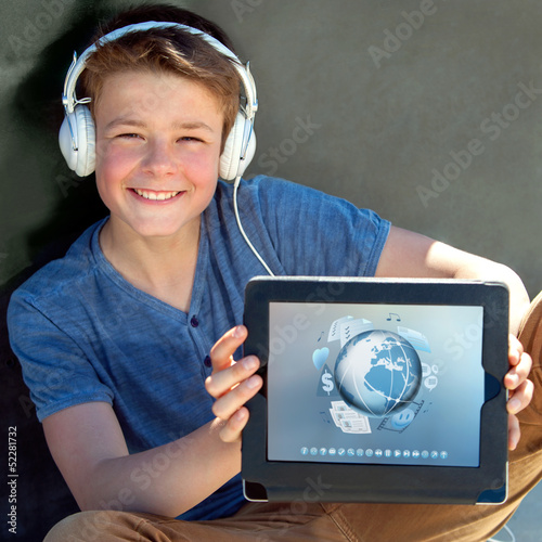 Cute boy showing tablet with multimedia symbols.