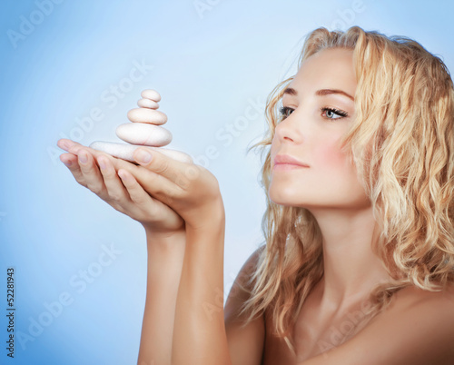 Cute woman with spa stones