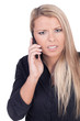 Worried young blond woman talking on mobile phone
