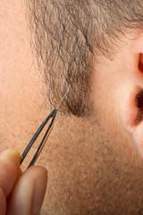 Mann entfernt erstes graues Haar mit Pinzette