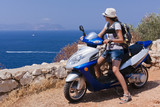 Young woman on a scooter is looking on blue Mediterranean sea.