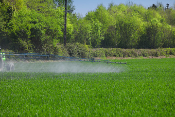 Close up of farming tractor spraying on green field