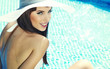 canvas print picture - Pretty woman in white bikini floating in swimming pool