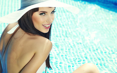 Pretty woman in white bikini floating in swimming pool