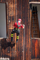 Fireman in uniform by climber and rock climber while descending