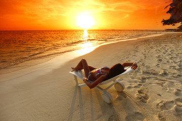 Woman in chaise-lounge relaxing on beach