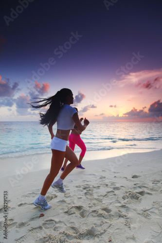 Two women running on beach