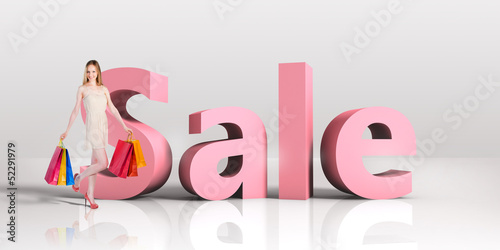 Young woman with shopping bags standing next to a word SALE