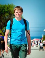 Adult sports guy strolling along the promenade