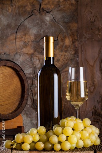 White wine, grapes, old bottle and a barrel.
