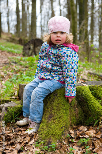 little girl is sitting on a stump