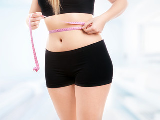 Size 40/42 woman is measuring waist
