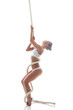 Flexible aerialist posing on rope in studio