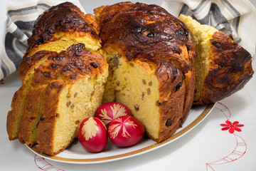 Panettone whith raisins and three Easter eggs on white plate