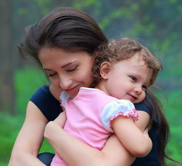 Smiling happy mother and cute kid girl cuddling outdoor summer b