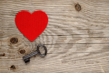 Red heart and vintage key on wooden background
