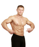 Muscular young man showing abs, isolated o white background