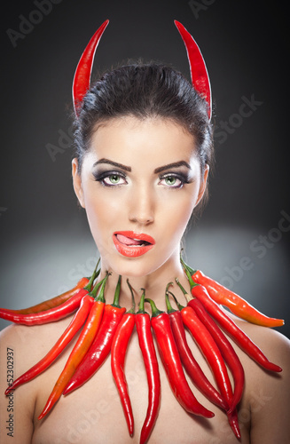 beautiful young woman portrait with red hot and spicy peppers