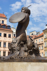 Symbol of Warsaw - mermaid over old Town colorful houses