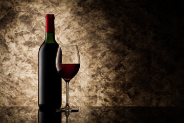 bottle with red wine and glass on a old stone
