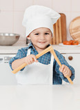 little boy holding a spaghetti cook in the hands of