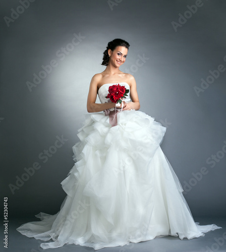 Charming bride with bouquet posing in studio