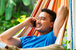 Young asian man in hammock with phone