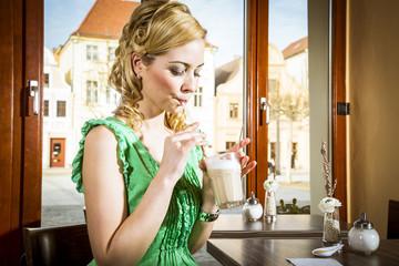 Hübsche blonde Frau mit grünem Kleid im Kaffee