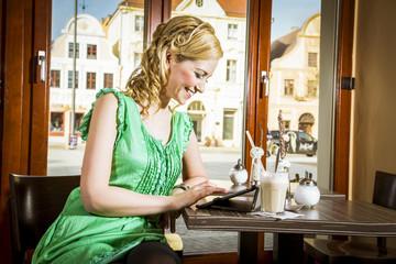 Hübsche blonde Frau in grünem Kleid mit Ipad im Kaffee