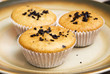 Freshly baked muffins in cups topped with chocolate .