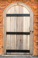 Vintage old wooden door on a red brick wall