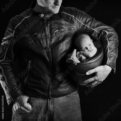 A motorcyclist father holds his newborn baby in his helmet