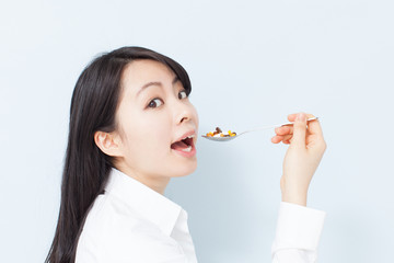 サプリメントを食べる女性