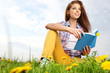 beautiful girl with book on grass