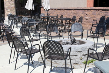 Outdoor restaturant with tables and chairs around fire pit