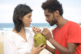 Multiethnic couple drinking coconut water