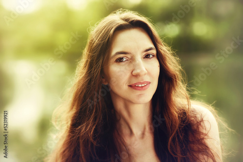 portrait of a young woman with a long beautiful hair outdoors .
