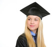 Happy young woman in graduation gown looking on copy space