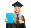 Young woman in graduation gown pointing book