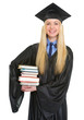 Portrait of smiling young woman in graduation gown holding books
