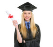 Happy young woman in graduation gown showing diploma