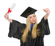 Happy woman in graduation gown with diploma rejoicing success