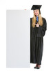 Happy young woman in graduation gown pointing on blank billboard