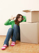 Young woman sitting on the floor near boxes