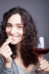 A beautiful young woman is tasting wine.