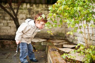 Cute boy gadening in his back yard