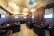 Stylish karaoke bar with armchairs and screens.