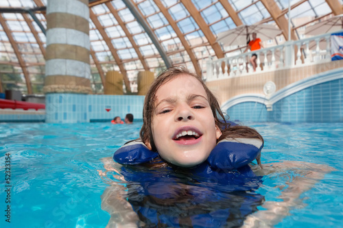 Happy girl in lifejacket in the clear blue water in water park.