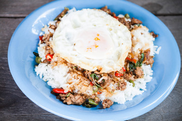 Thai spicy food, rice topped with stir fried pork and basil with